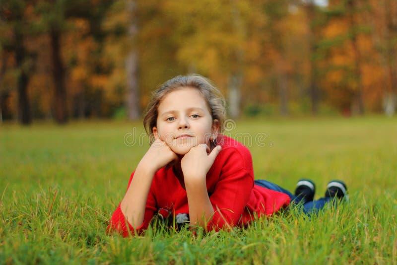Flickan ligger på det gröna gräset i parkera arkivfoto