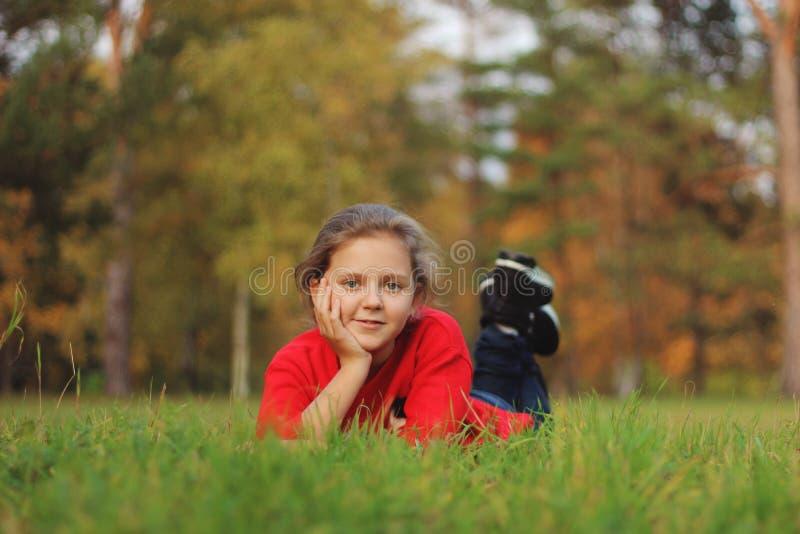 Flickan ligger på det gröna gräset i parkera fotografering för bildbyråer