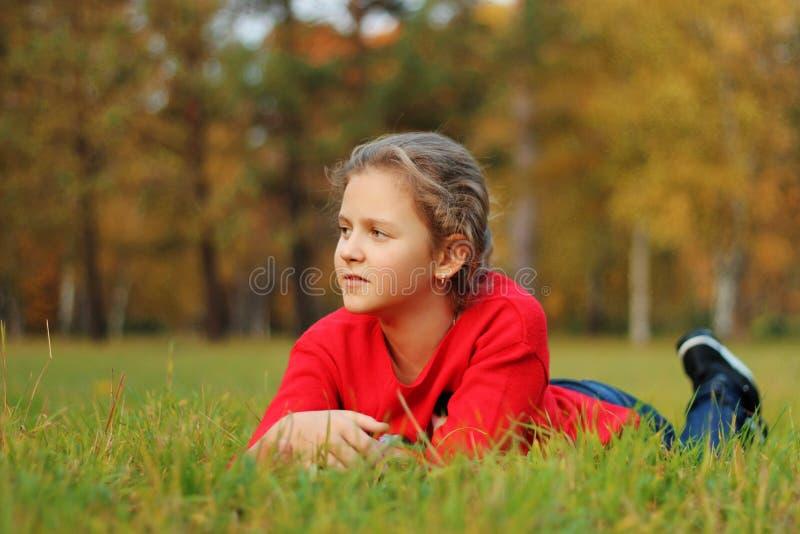 Flickan ligger på det gröna gräset i parkera arkivbild