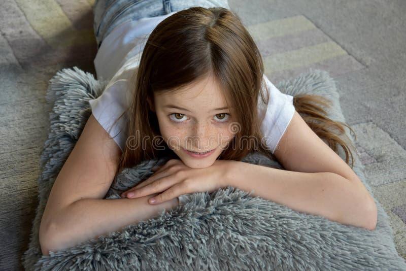Flickan ligger på golvet royaltyfri foto