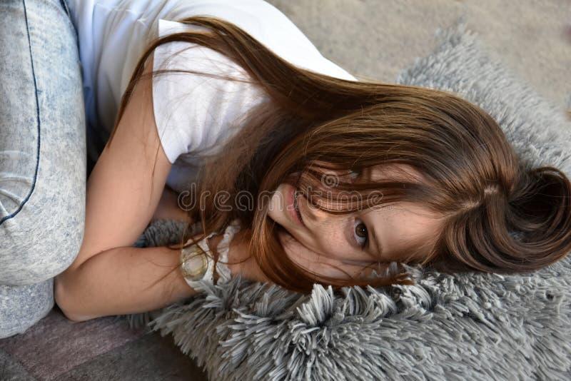 Flickan ligger på golvet royaltyfri fotografi