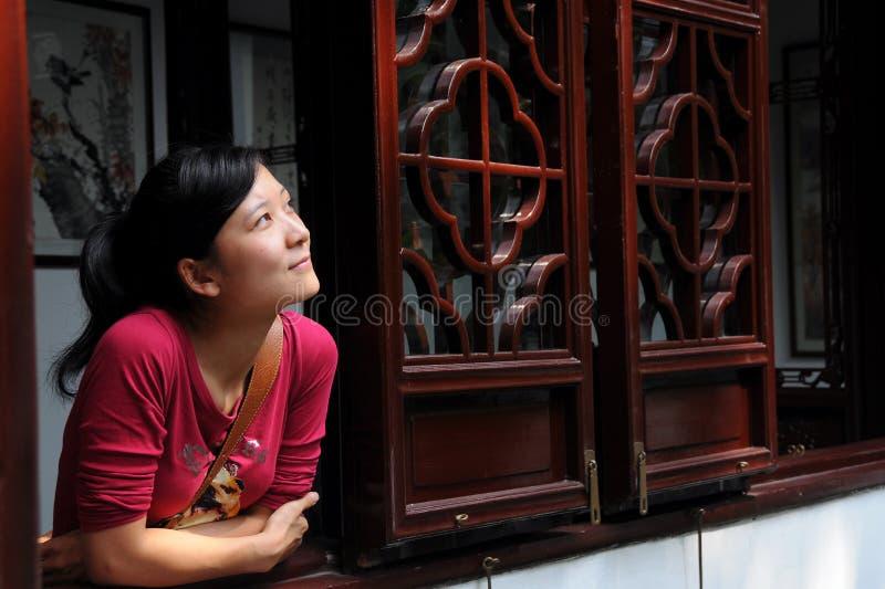 flickan lutar fönstret royaltyfri fotografi