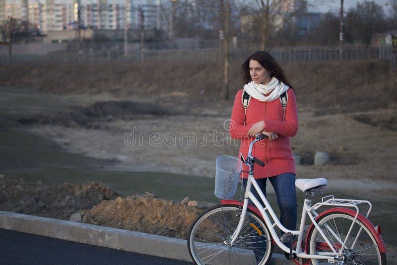 Flickan lutar på en parkerad cykel Vila på vårcirkuleringen royaltyfri fotografi