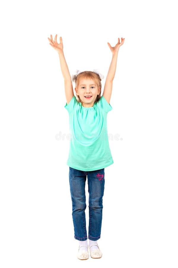 Flickan lyfter hennes armar upp och leenden royaltyfri foto