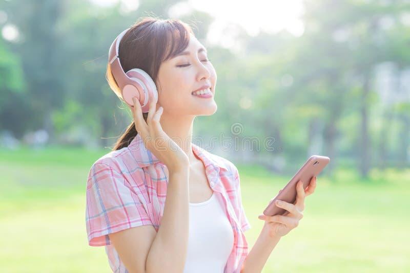 Flickan lyssnar musik med hörlurar royaltyfri bild