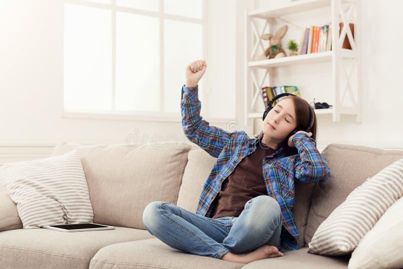 Flickan lyssnar till musik i hörlurar hemma arkivbilder