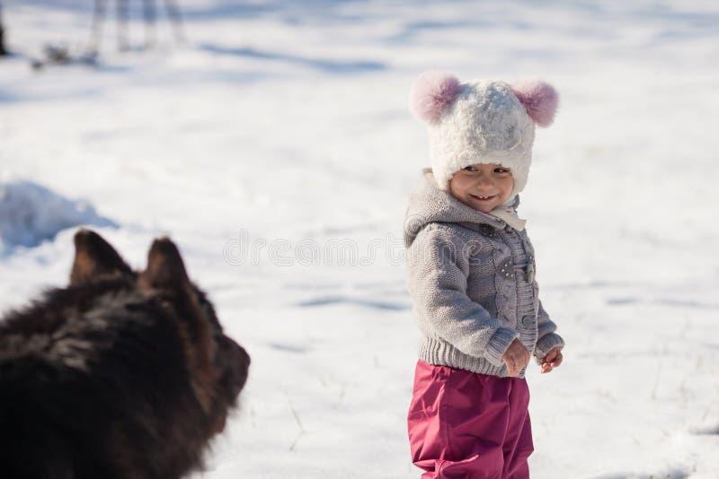 Flickan möter en hund på vinter går royaltyfria bilder
