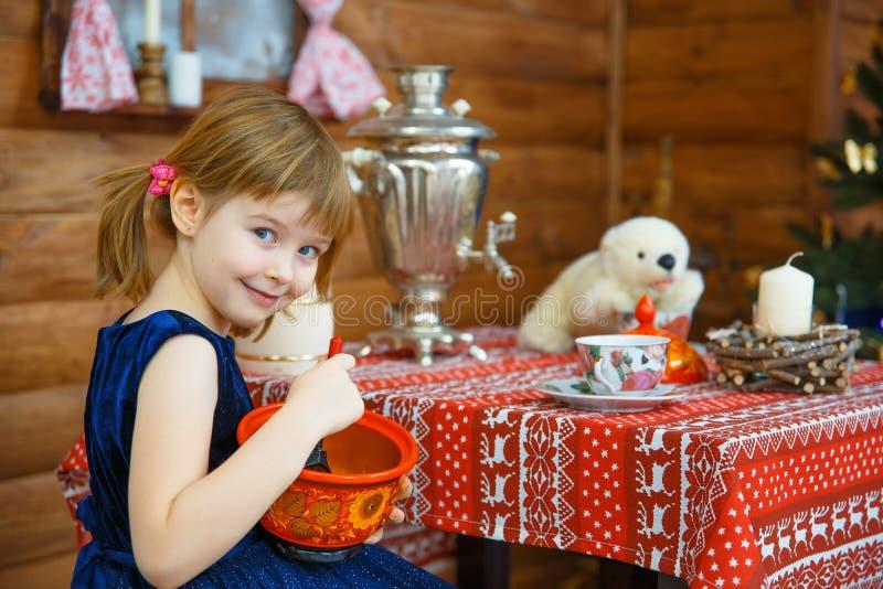 Flickan Masha lagar mat havregröt royaltyfria bilder