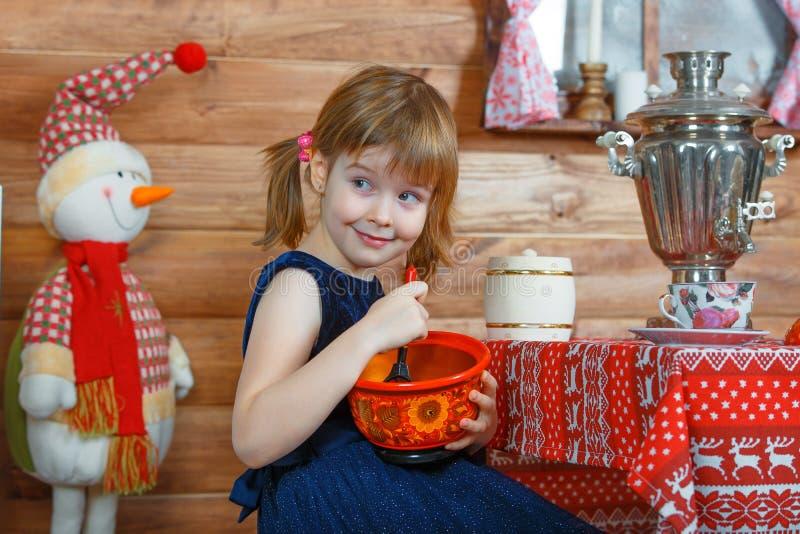 Flickan Masha lagar mat havregröt royaltyfri fotografi