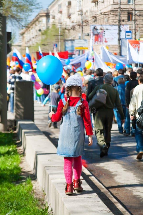 Flickan med ballongtagande särar i demonstrationen för den Maj dagen i Volgograd royaltyfria bilder
