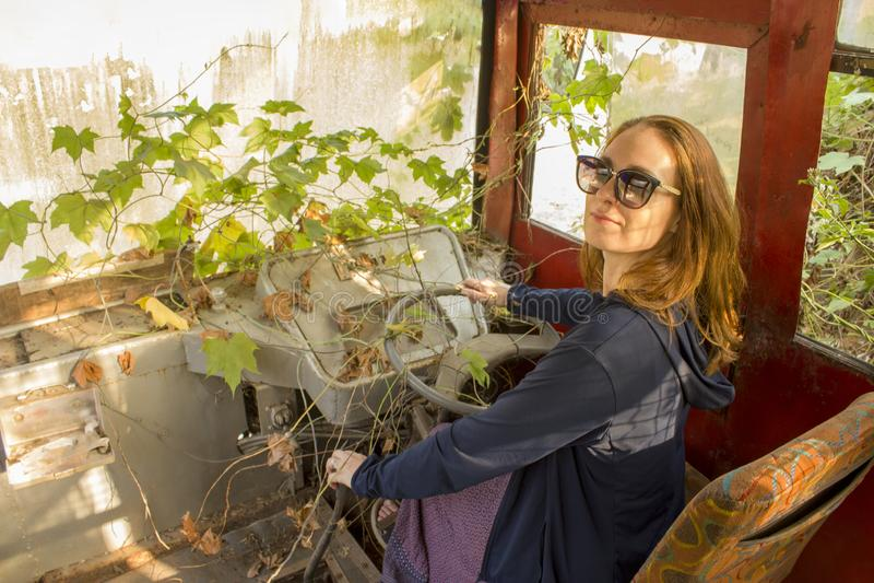 flickan med blont hår i solglasögon sitter och ler på förarsätet i en övergiven murgröna-täckt buss royaltyfri bild