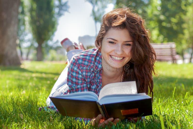Flickan med boken i sommaren parkerar royaltyfri foto
