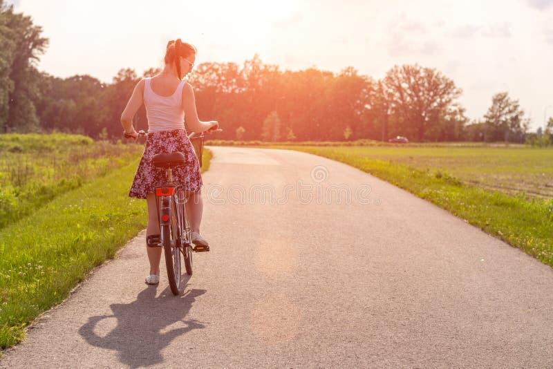 Flickan med cykeln p? sommarsolnedg?ngen p? v?gen i staden parkerar Cirkuleringscloseuphjul p? suddig sommarbakgrund Cykla ner t arkivbild