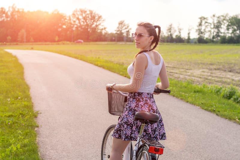 Flickan med cykeln p? sommarsolnedg?ngen p? v?gen i staden parkerar Cirkuleringscloseuphjul p? suddig sommarbakgrund Cykla ner t fotografering för bildbyråer