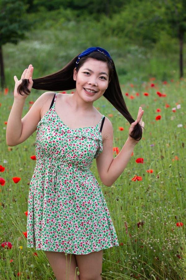 Flickan med den blåa musikbandet spelar med hennes hår i vallmofält fotografering för bildbyråer