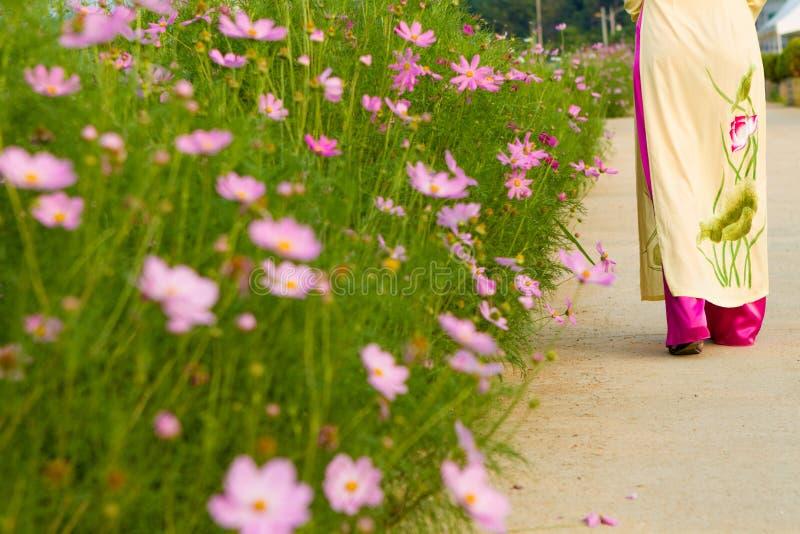 Flickan med den långa klänningen går i blommaträdgården arkivbilder