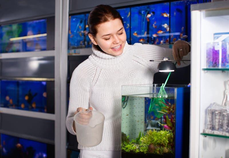 Flickan med den netto och vattenbehållaren ska fånga barnsliga fis arkivfoton