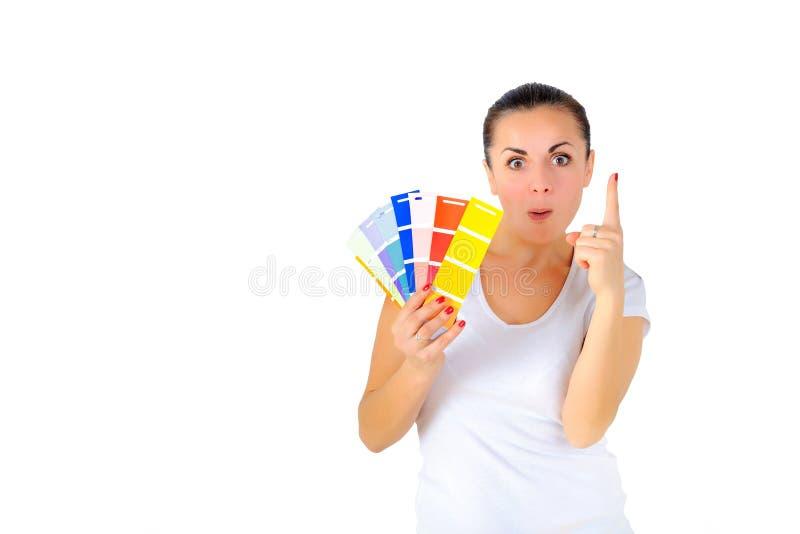 Flickan med den roliga framsidan väljer målarfärgfärg royaltyfri foto