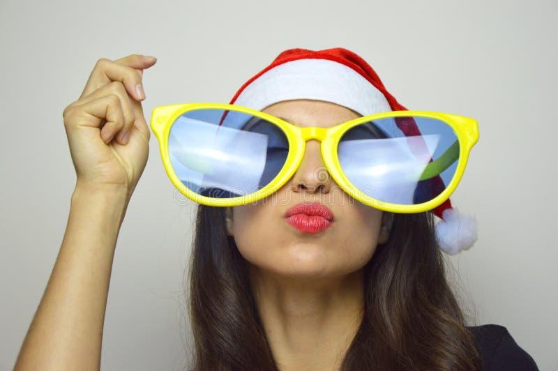 Flickan med den stora roliga solglasögon och Santa Claus hatten firar jul fotografering för bildbyråer