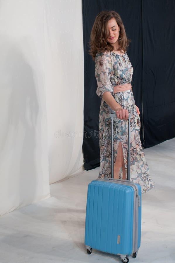 flickan med den trendiga fantasiblommaklänningen med gördelen, med blått reser påsen arkivfoton