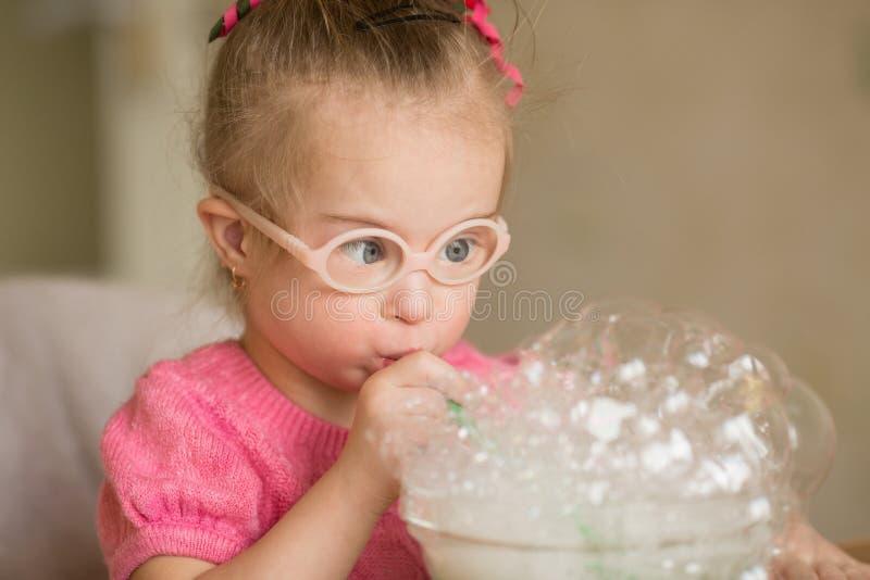 Flickan med Down Syndrome gör övning för andninganförandeterapi royaltyfria bilder