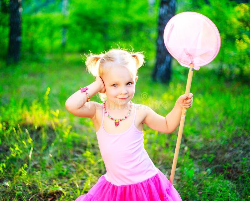 Flickan med en fjäril förtjänar arkivfoto