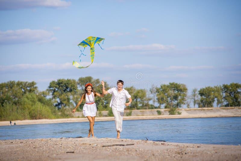 Flickan med en grabb kör drakeflyg på stranden i våren, sommar arkivbilder
