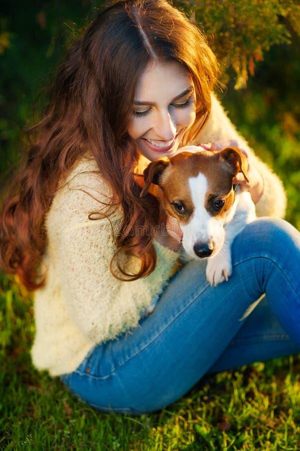 Flickan med en hund Jack Russell Terrier parkerar in arkivfoto