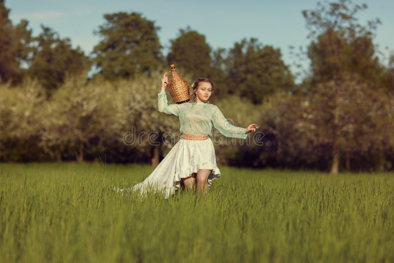 Flickan med en kanna är på fältet med gräs royaltyfria foton