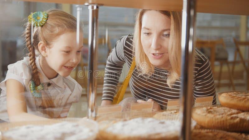 Flickan med en råttsvans och hennes mamma ser pajerna i fönstret som väljer royaltyfri foto