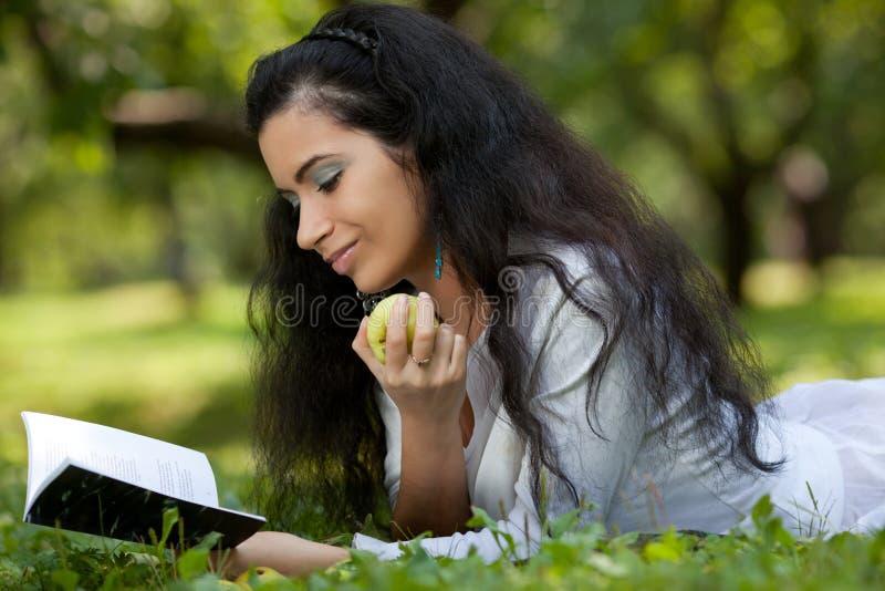 Flickan med ett äpple och boken på ett gräs arkivfoton