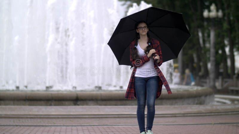 Flickan med ett paraply i parkerar på en bakgrund av en springbrunn royaltyfria foton