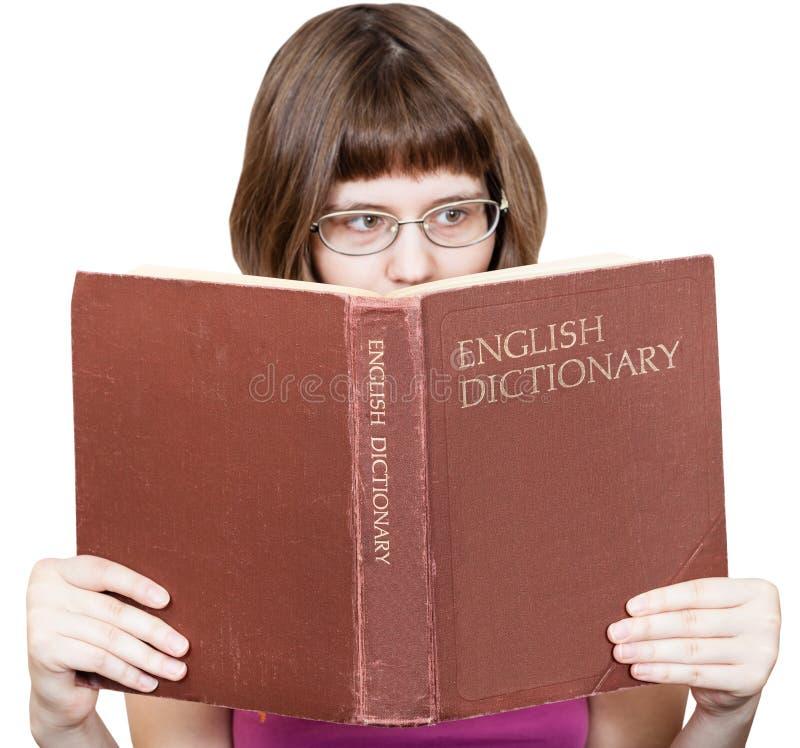 Flickan med exponeringsglas läser den engelska ordbokboken arkivbild