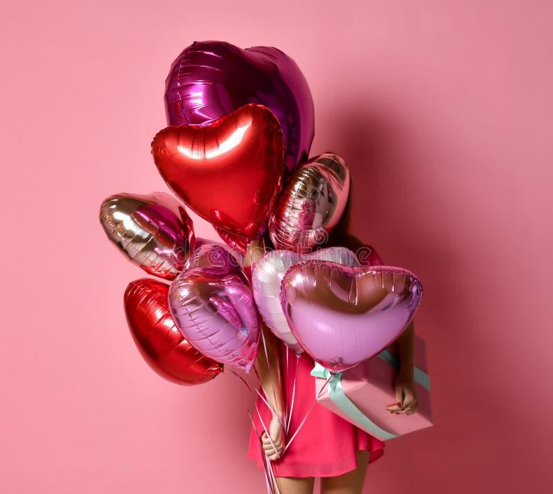 Flickan med färgrika hjärtor luftar ballonger som döljer bakom på födelsedagferiepartiet som har gyckel och firar med gåvan royaltyfria bilder