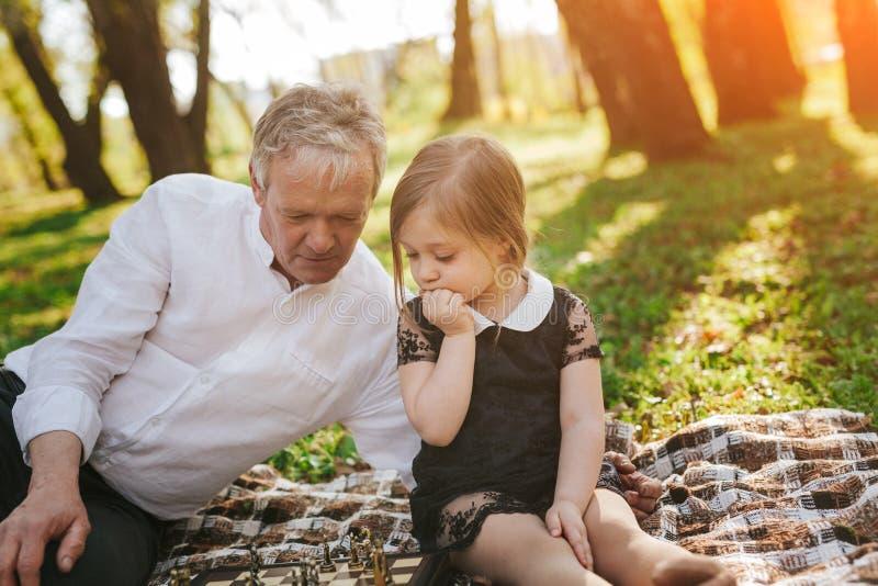Flickan med farfadern som spelar schack parkerar in arkivbilder