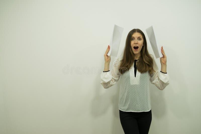 Flickan med flödande hår och en öppen mun i chock står på rätten som rymmer vita ark i hennes händer som rymmer dem till hennes e royaltyfri foto