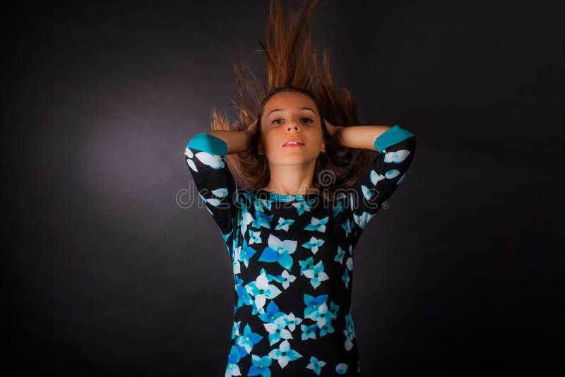 Flickan med framkallning av l?ngt h?r p? svart bakgrund arkivfoto