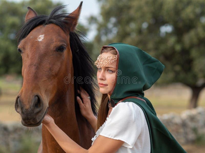 Flickan med grön udde smeker huvudet av en brun häst royaltyfria bilder