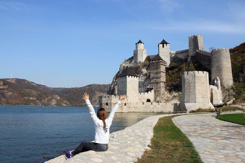 Flickan med händer upp blickar på den Golubac fästningen royaltyfri foto