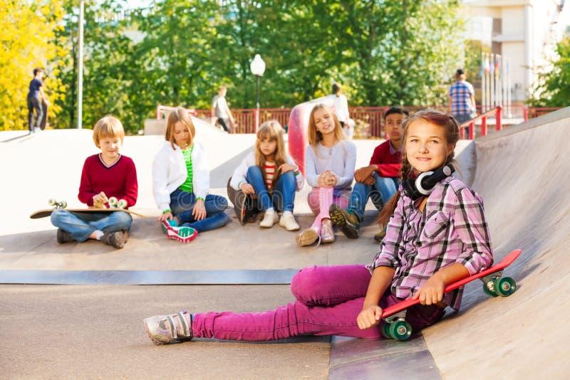 Flickan med hörlurar rymmer skateboarden och parar ihop fotografering för bildbyråer