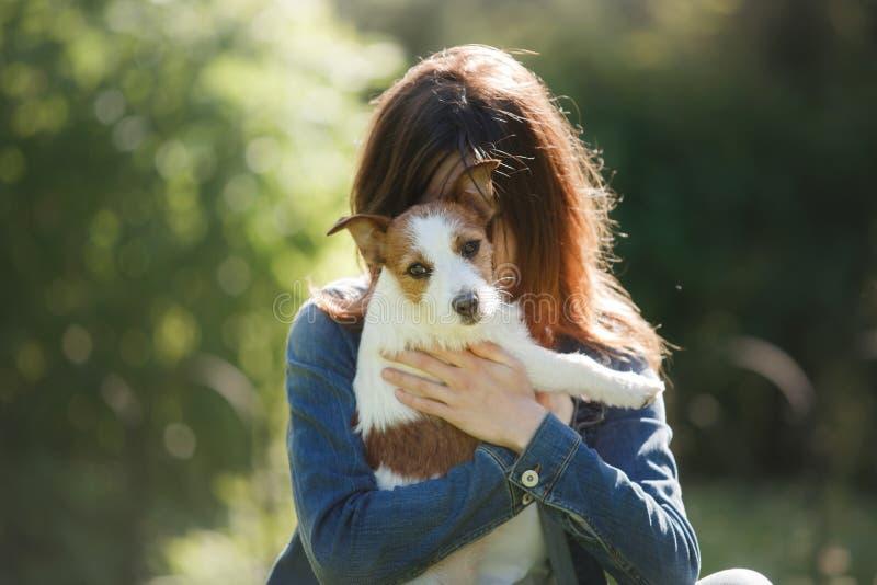 Flickan med hunden i henne armar Lite Jack Russell Terrier royaltyfri bild