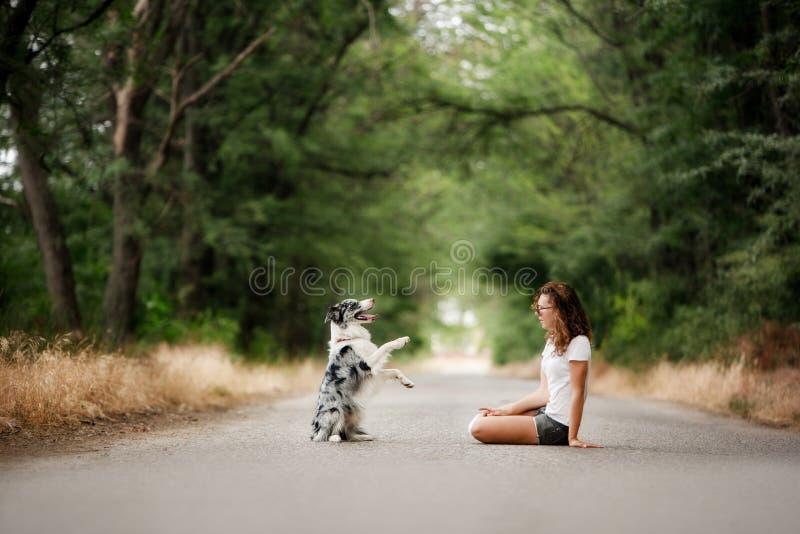 Flickan med hunden sitter på vägen i skog hunden gör ett trick arkivbild