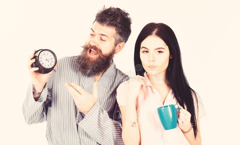 Flickan med kaffekoppen, manh?ll tar tid p? i hand Par familj vaknade upp i r?tt tid F?r?lskade par, ung familj i pajama royaltyfri fotografi