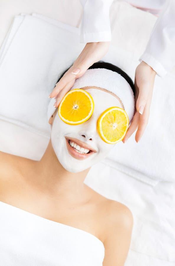 Flickan med kräm på framsida och apelsinen klipper på ögon arkivbild