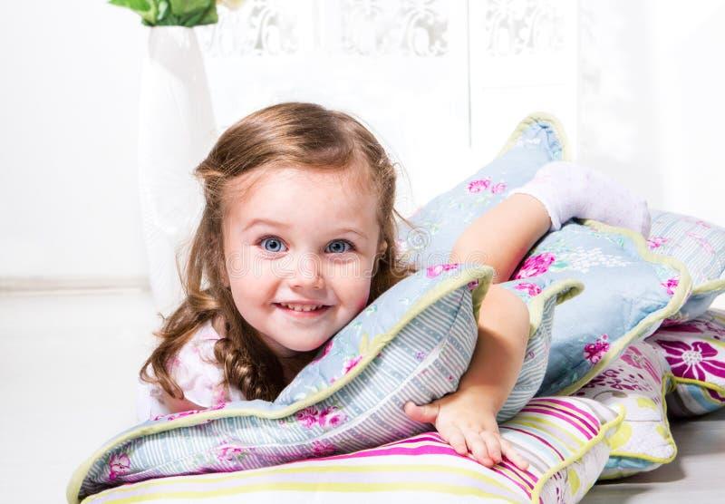 Flickan med kudder royaltyfri fotografi