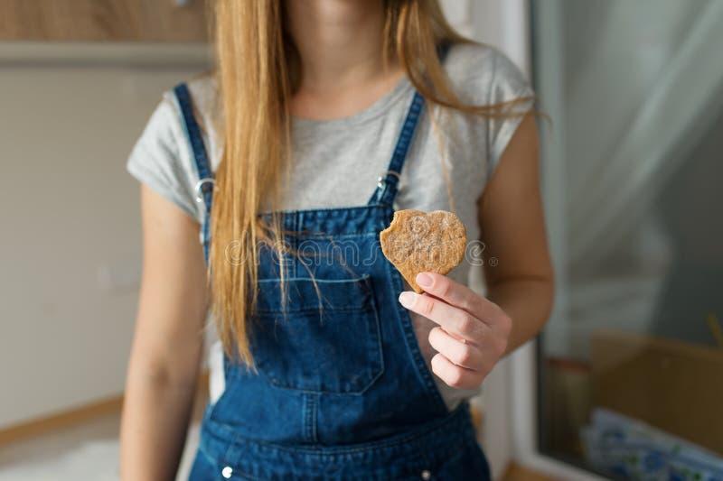 Flickan med långt hår föreslår för att äta ljust rödbrun kakor royaltyfria bilder