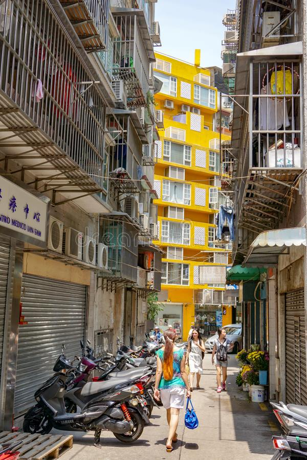 Flickan med långt hår från baksida går Macao den smala gatan royaltyfri bild