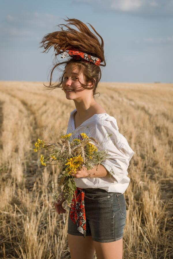 Flickan med långt hår på halmfält med vildblombukett arkivfoto