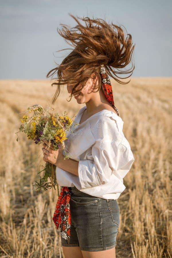 Flickan med långt hår på halmfält med vildblombukett arkivbilder