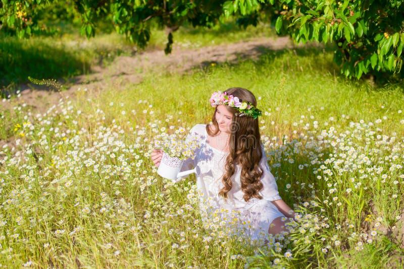 Flickan med långt hår som bär en krona av tusenskönor på fältet fotografering för bildbyråer